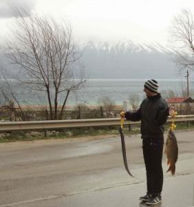Visser bij Lake Ohrid met aan de overkant Macedonie